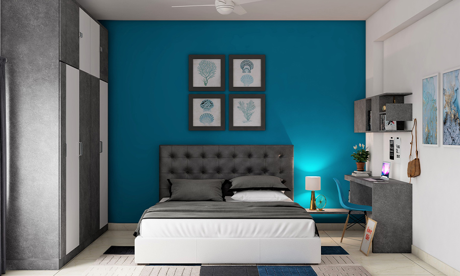 Dark teal colour paint on one accent wall pairs well with grey accents and creative wall paintings in the bedroom.
