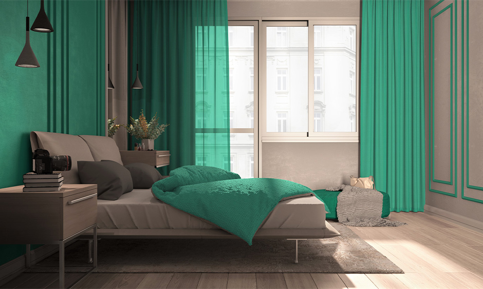The double bed with pillows and the side tables and wall in light teal paint colours gives the bedroom a luxurious makeover.