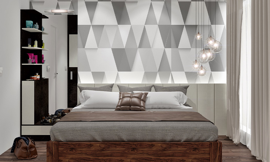 Master bedroom has 3d triangle wall paint in varying shades of grey and white and lends a sleek look to space.