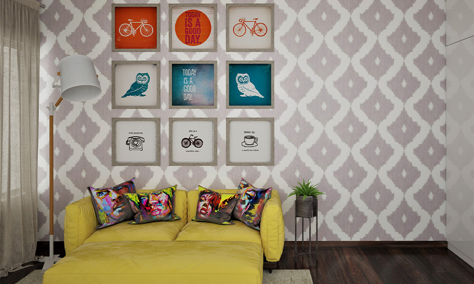 Ikat wall geometric painting blends in perfectly with multiple picture frames and bright yellow sofa cum bed.