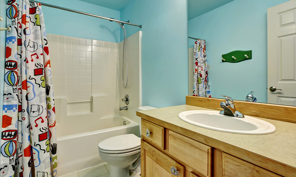 Kids bathroom ideas bathtub with a child-friendly grab bar and cartoon shower curtain add some playfulness to the area.