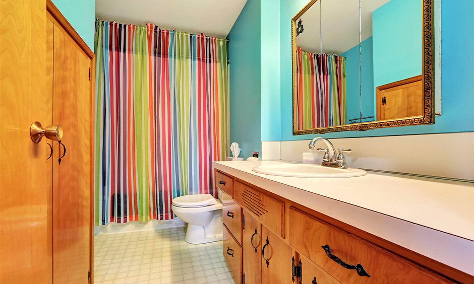 Light blue-toned kids bathroom decor with brightly-striped shower curtains & lower wooden cabinets look fun and inviting.