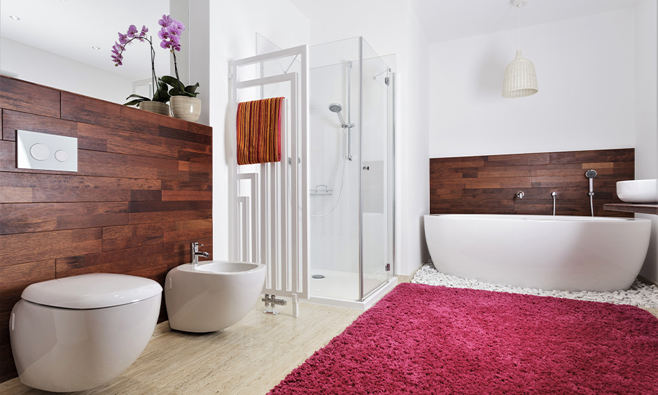 Bathroom with medium-sized pink and white-coloured rug and wooden panels on each side is a little girl bathroom decor.