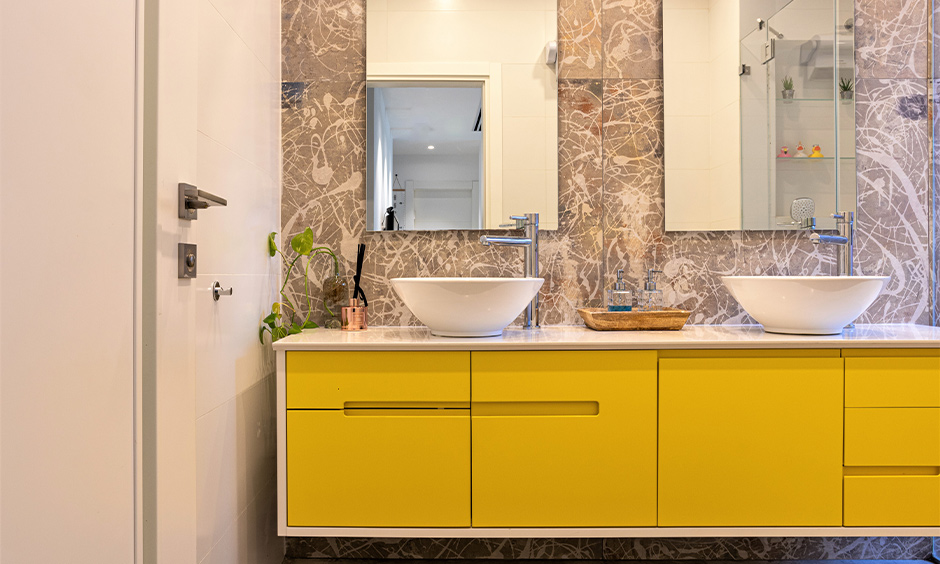 Lower height yellow cabinet blends with the patterned backsplash walls are children bathroom design for hassle-free.