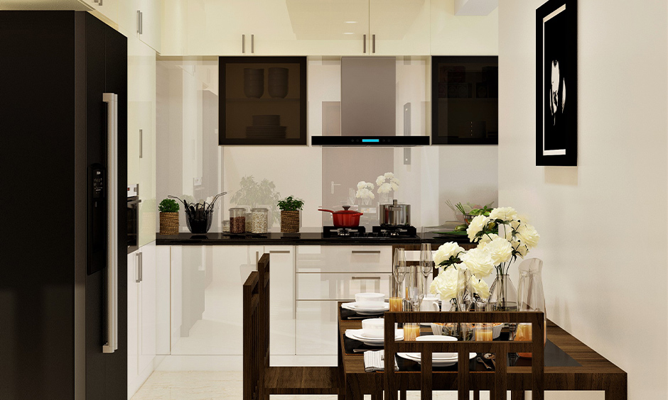 White and cream PVC kitchen cabinets in kitchen cum dining area look aesthetic.