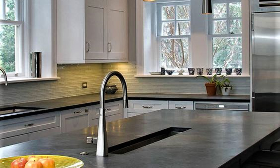 Black photos of soapstone countertops which embellishes the grey and off-white kitchen