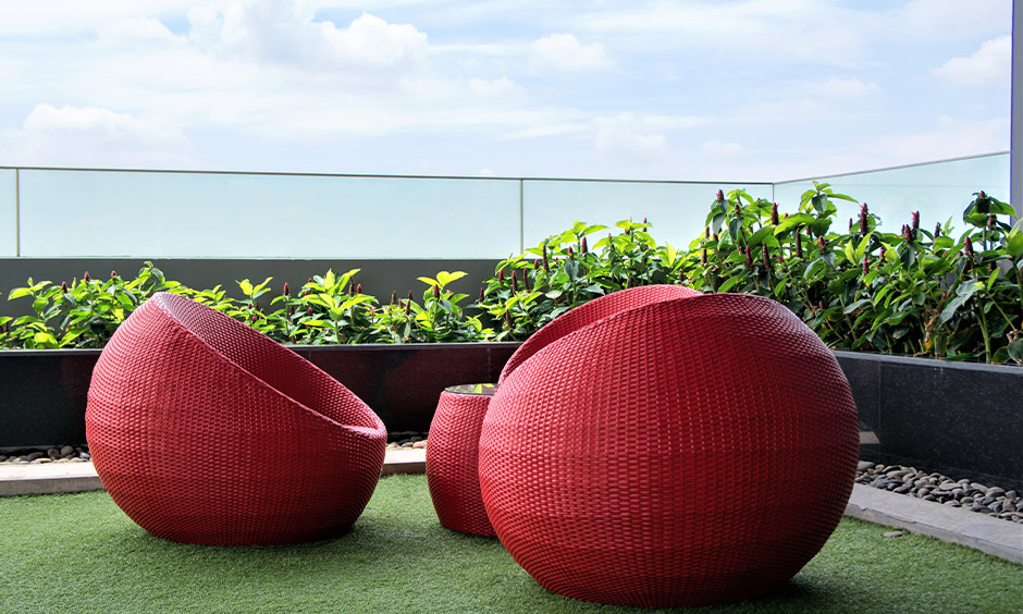 Apartment seating for balcony with red rattan spherical chairs and green turf on the floor brings some freshness.