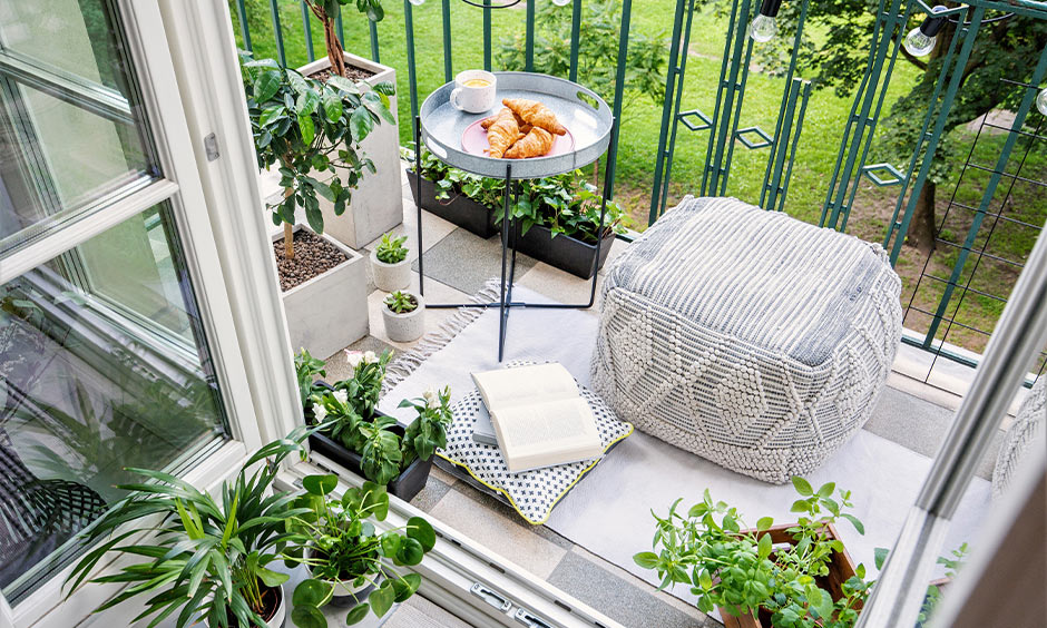 White and green-themed DIY balcony seating with a pouffe, rug, small cushion and natural potted plants looks classy.
