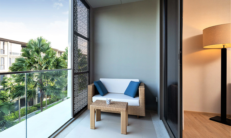 Rectangular balcony seating area with a jute two-seater sofa & table in the corner, steel and glass railings looks gorgeous.