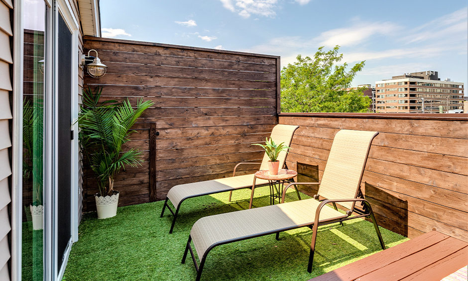 A pair of lawn chairs laid out on the green turf that is surrounded by the wooden walls is balcony seating design.