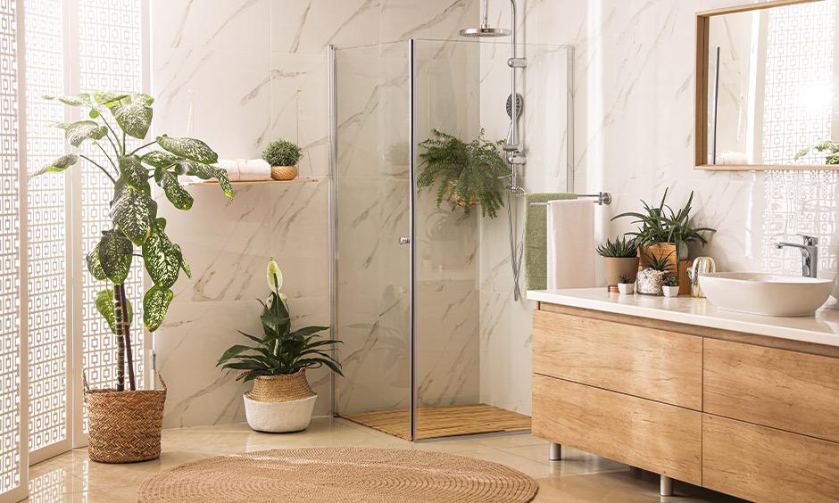 Glass enclosure shower and a plethora of planters around creates a natural bath with bohemian contemporary bathroom interiors.