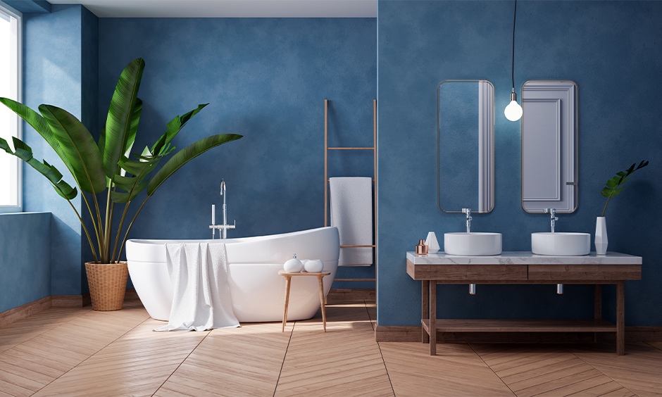 Blue and cool white tropical contemporary bathroom designed with the luxe fittings and indoor planters looks soothing.