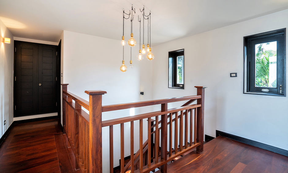 Classic indoor wood stair railing design with industrial hanging lights above accentuate and ooze warmth into space.