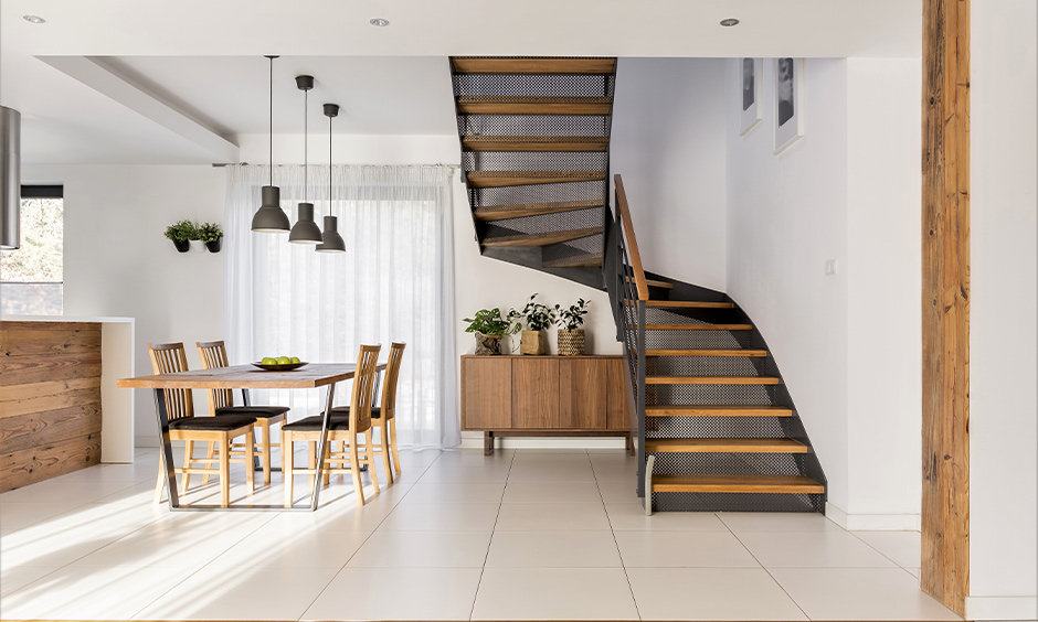 Industrial metal staircase with wooden treads and handrail gives a softness to the bold is the modern wooden railing.