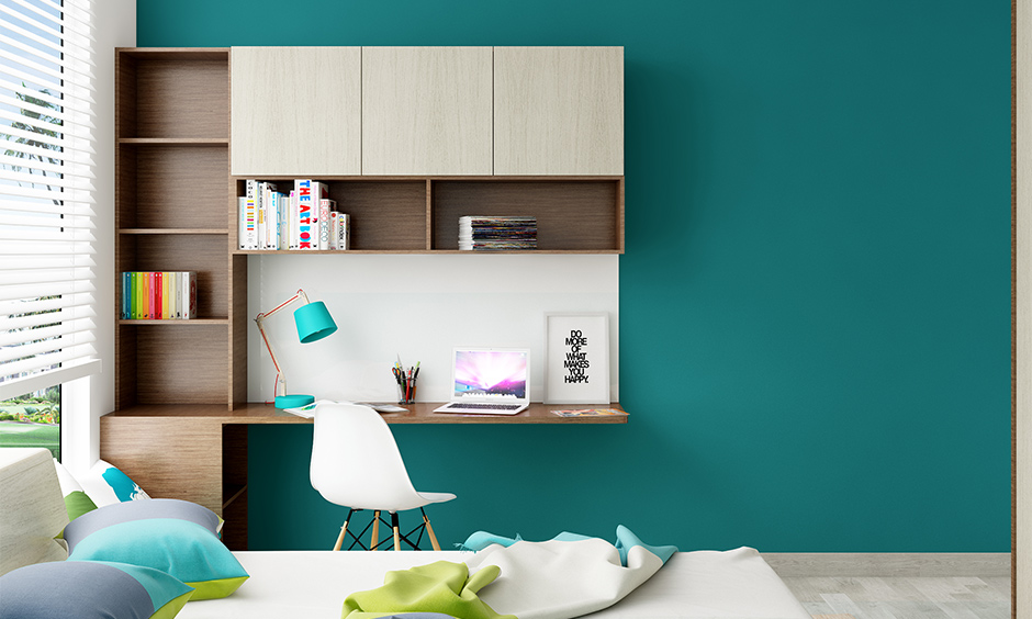 Wall attached study table with shelves in brown and cream laminate against the blue wall looks minimalistic.