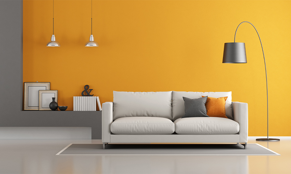 Sleek black metal minimal tall lamp for living room blends in beautifully with the orange wall and white sofa.