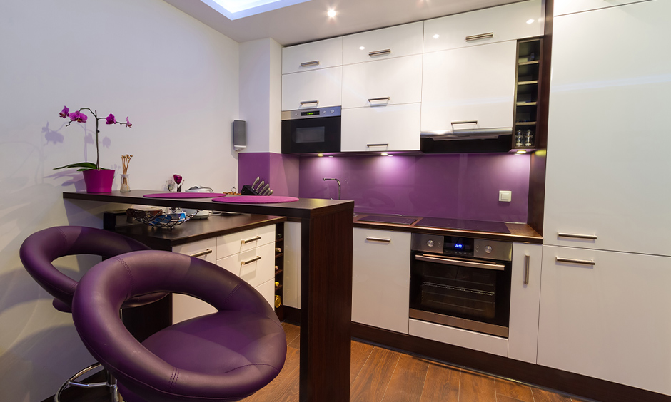 Backsplash coloured in purple and white kitchen with dining table and chairs in purple add vibrancy to space.