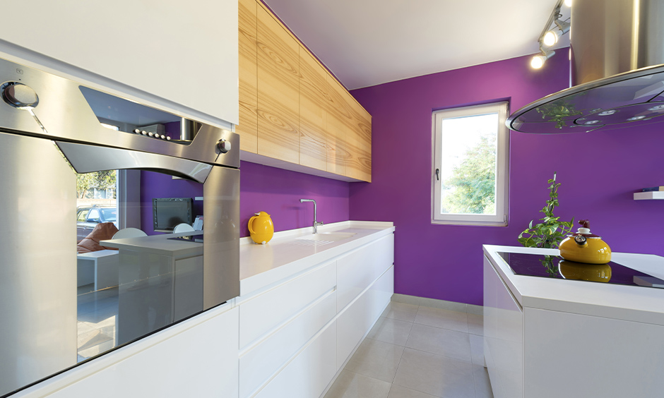 A mix of retro and modern kitchen with purple wall and white cabinets add a cosy charm are the purple kitchen design ideas.