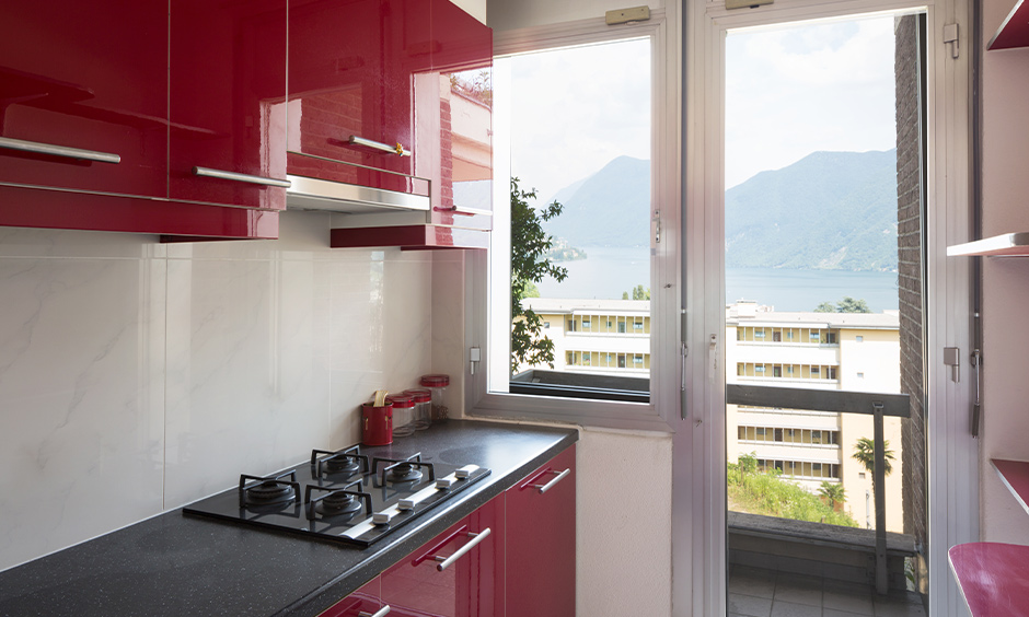 Cabinets laminated in red kitchen design image with a black countertop lends an intriguingly refreshing vibe to space.