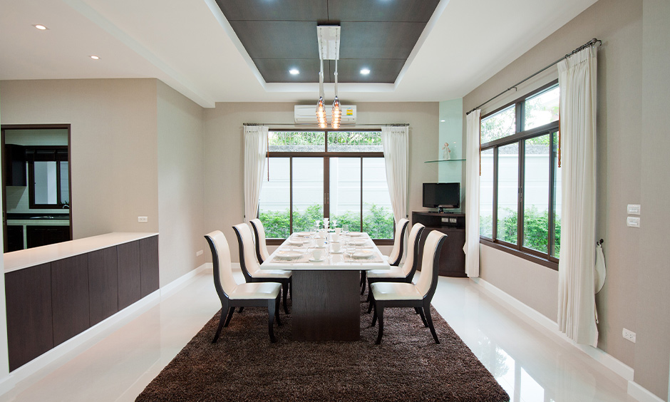 The dining room has hanging ceiling lights, a six-seater table in white and white vitrified tiles flooring suave look.