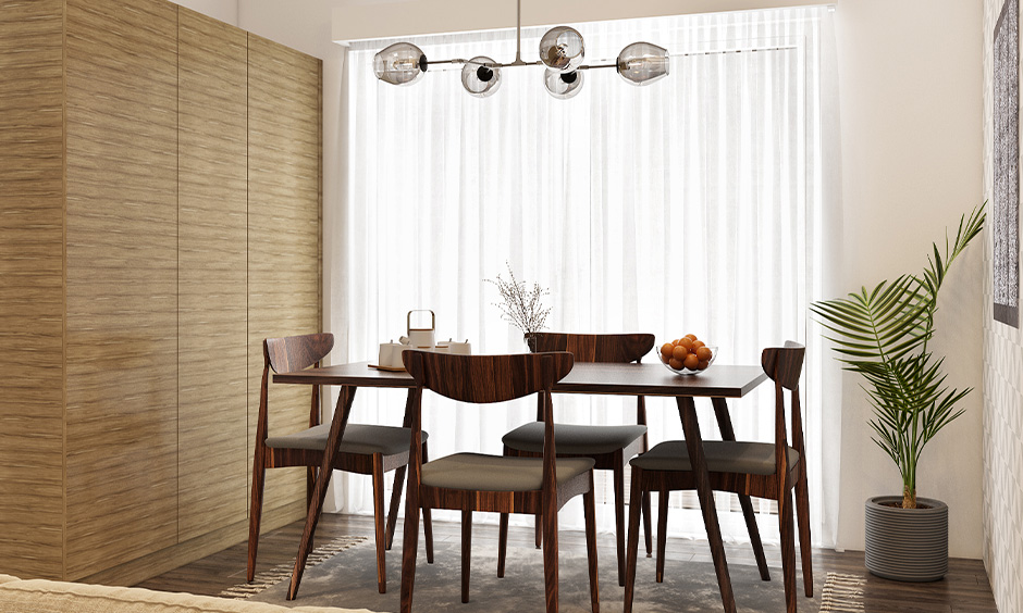 Dining room with hanging light fixtures in transparent glass domes and a dining table made in a softwood look rustic.
