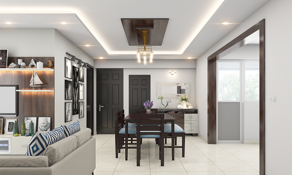 Living room cum dining hall ceiling designed in dark wood with cove and recessed lighting which brightens up the area.