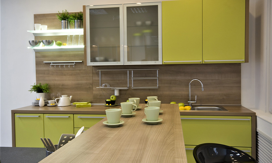 Glass corner shelf design for kitchen with a combination of green and light brown colour adds glow and class to the area.