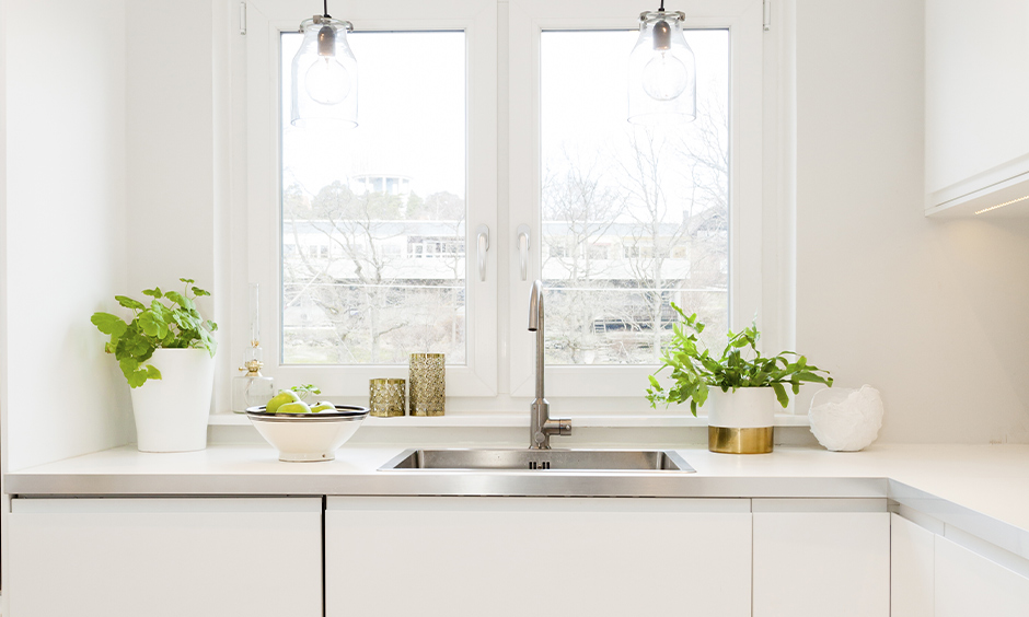 The classy white window makes it look more spacious in this white kitchen window design in India with hanging lights.