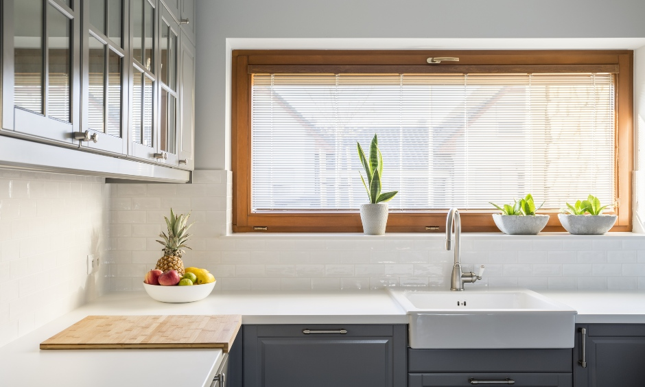 Small kitchen with wooden frame window truly stands out as an iconic focal point is the kitchen window design India.