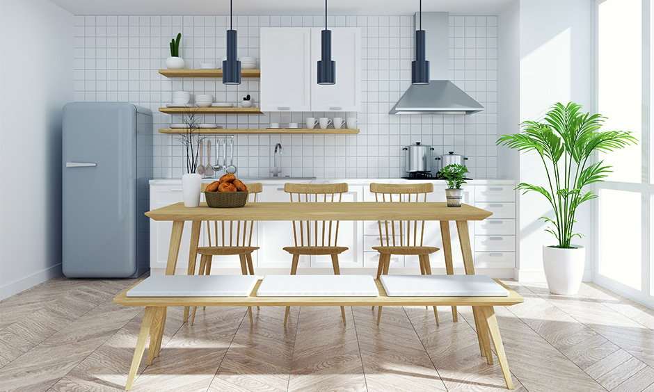 Picnic style bench and wooden chairs for dining room table in the one-wall white kitchen look elegant.