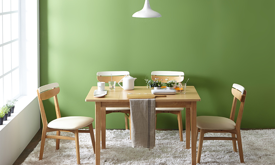 Small dining room table and chairs against a green accent wall with drop downlight look rustic.