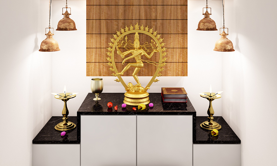 Dropdown lights on both the side of the idol are the pooja room decoration lights with cabinets and back wooden panel.