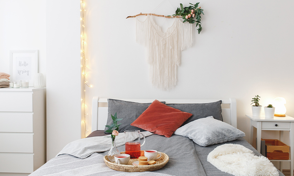 White bedroom with a piece of wall art and fairy lights in vertical look elegant is the best fairy lights for bedroom.