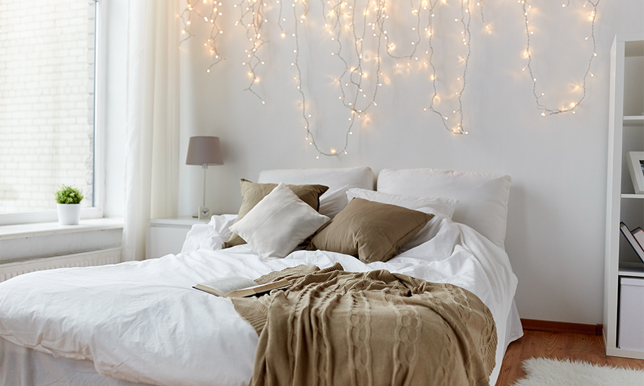 White bedroom with Queen-sized bed and dangling fairy lights for bedroom wall look lucent.