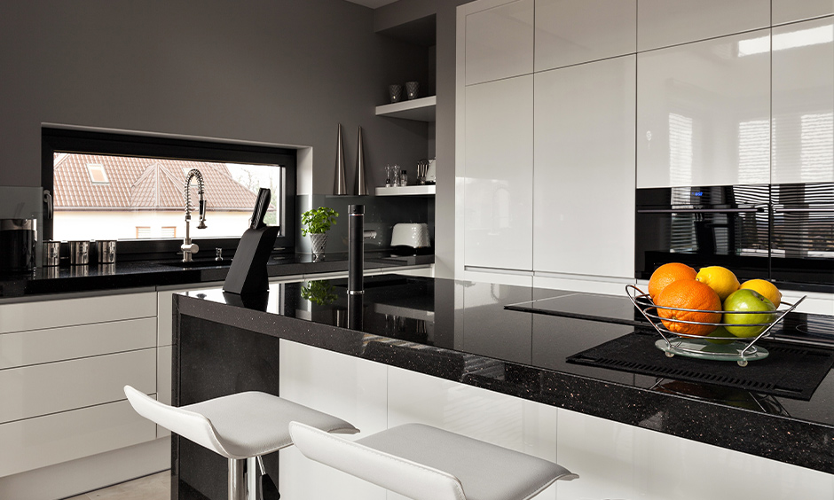 Galaxy black granite countertops with white cabinets in grey kitchen island create an overall eye-catching kitchen design.