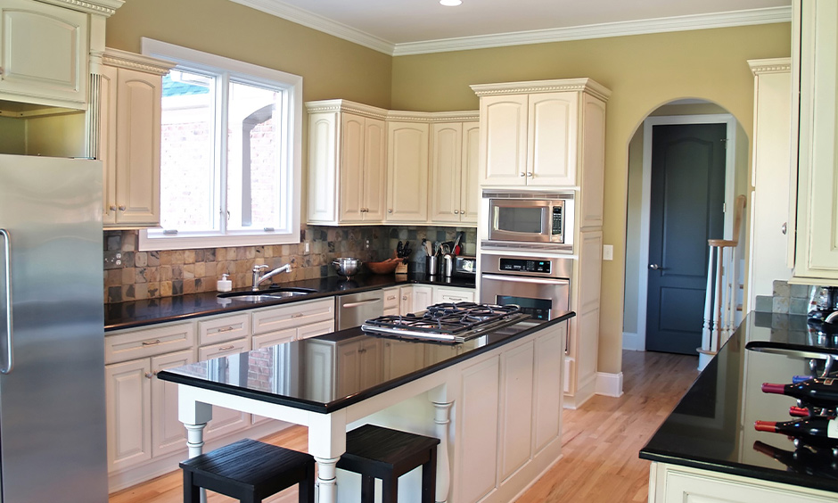 Classic island kitchen with absolute black granite countertops and white cabinets looks pretty and sleek.