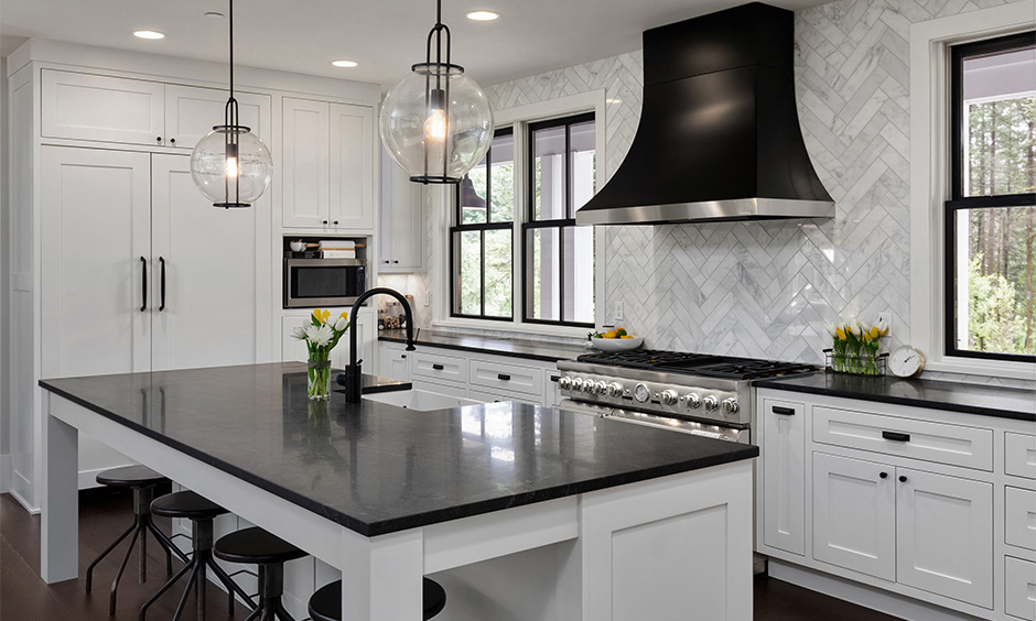 White island kitchen has Ubatuba black granite countertops with white cabinets that look aesthetic.