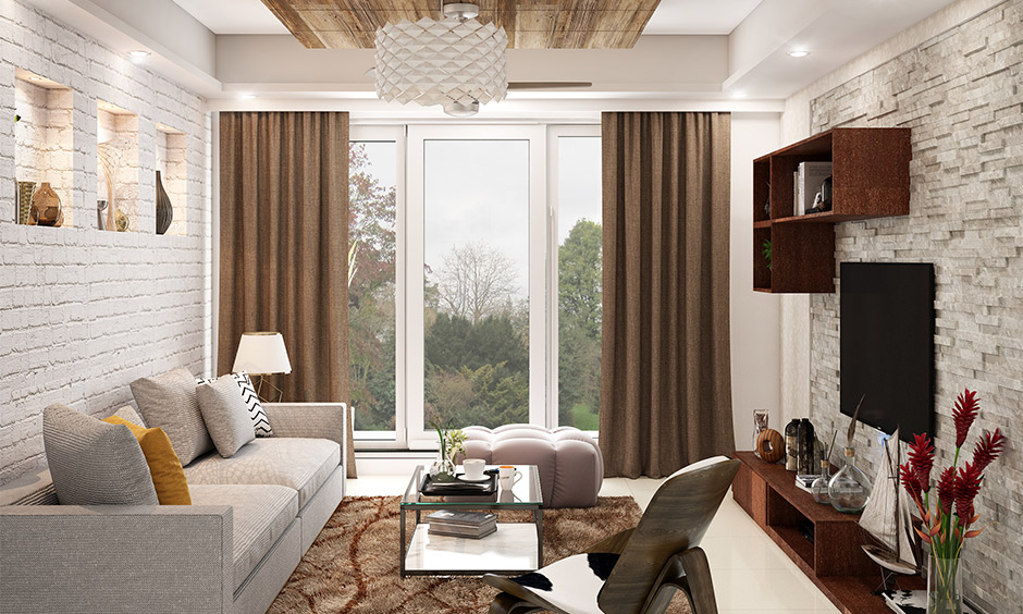 Living room with stone cladding, false ceiling and chandelier in 3 bhk interior design cost varies.
