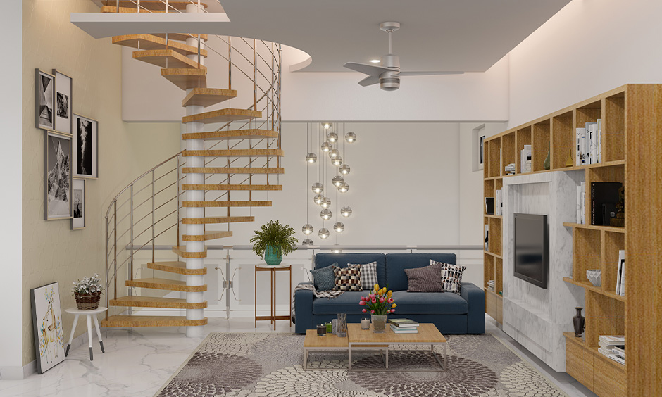 Elegant living room with a swirling staircase and a TV unit with ample storage is the best interior design low cost.