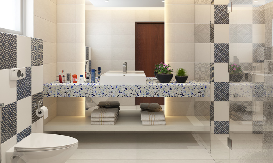 Modern bathroom low-cost interior design with textured tiles and a white granite countertop look elegant.