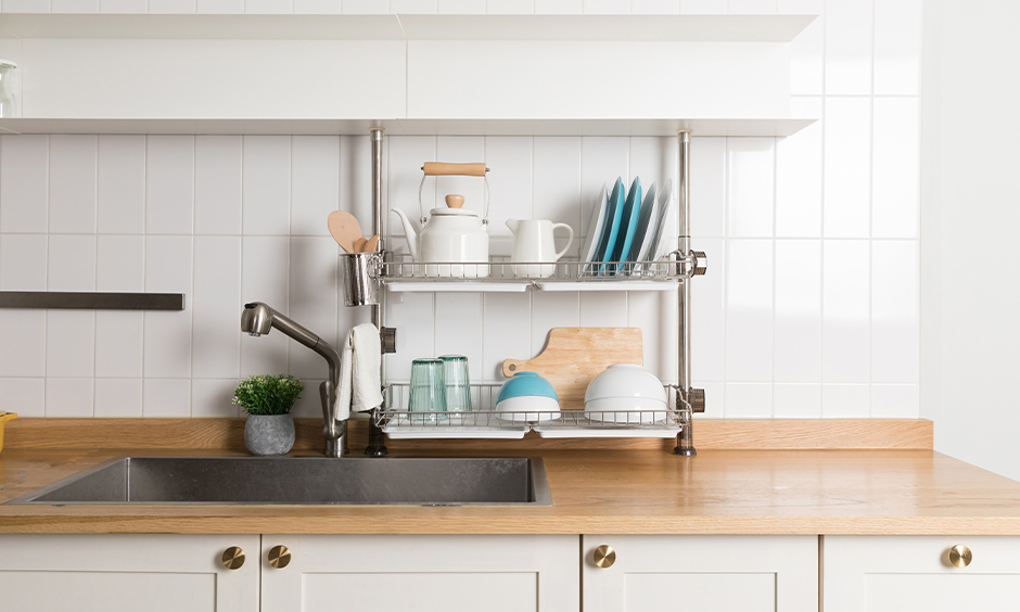 Over the kitchen sink shelf stainless steel segregated utensils in two-level to place plates, spoons and bowls.