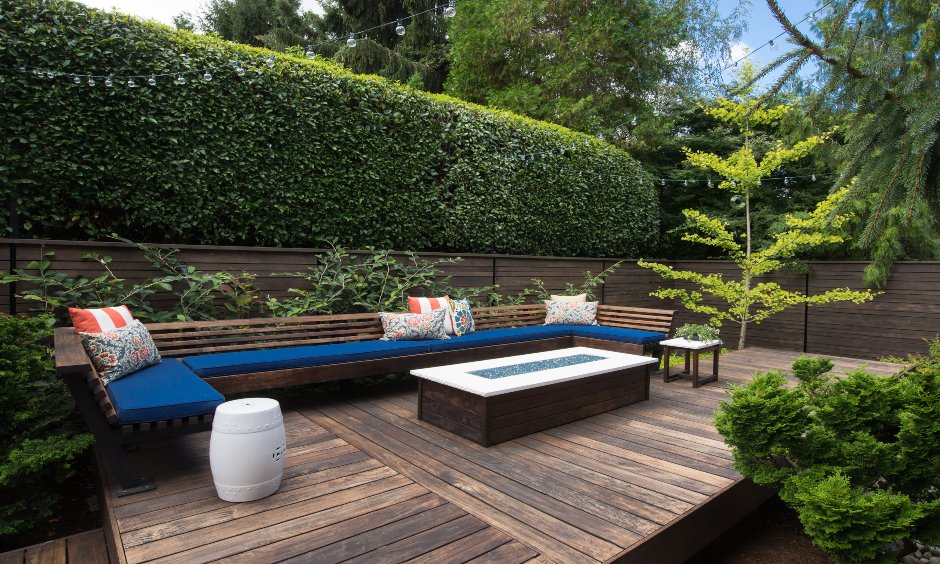 Minimal terrace garden with comfy seating, warm wooden aesthetics and landscaped surroundings is open terrace garden ideas.