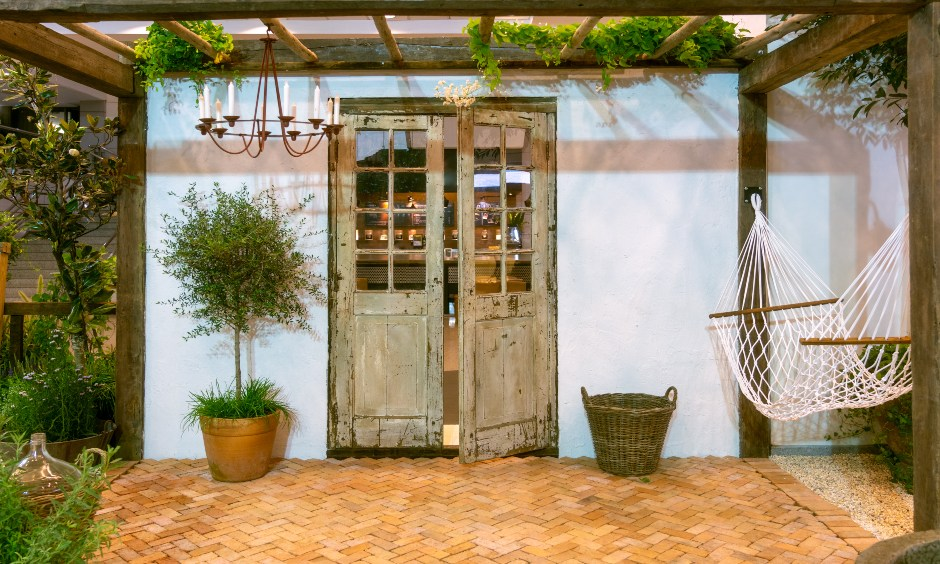 Small terrace garden design in a rustic theme with a hammock aligned with lush planters looks elegant.