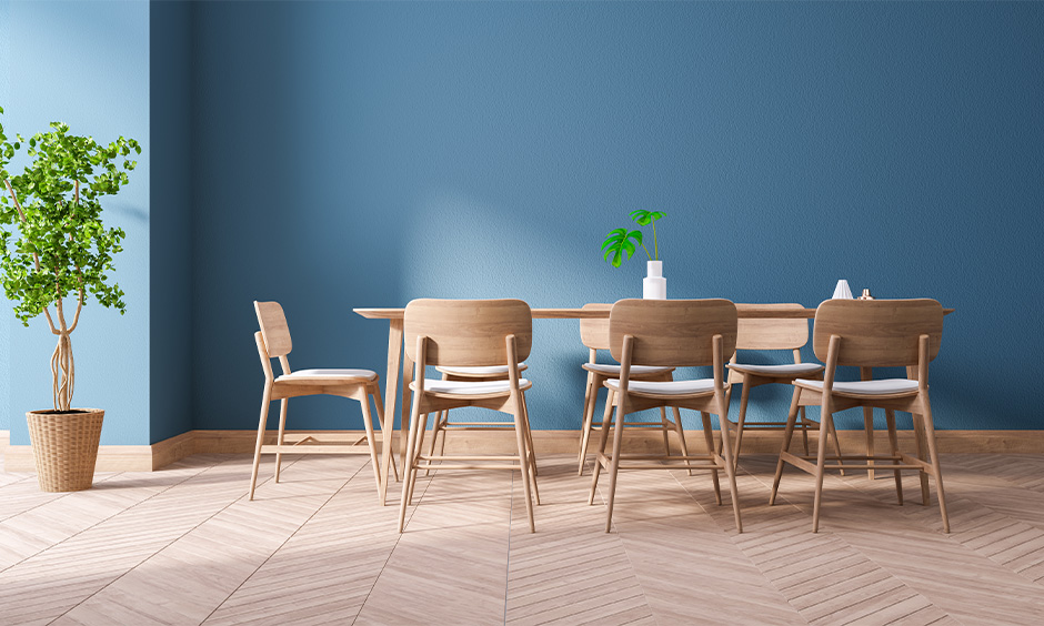 Light and stackable dining room chairs crafted from fibre against the blue wall, and they are very convenient to set up.