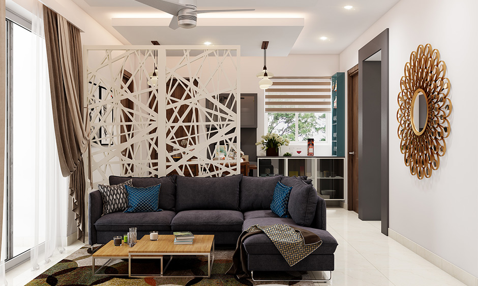 Partitioned drawing room decorated with an ornate mirror piece, false ceiling and sofa is how to decorate a drawing-room.