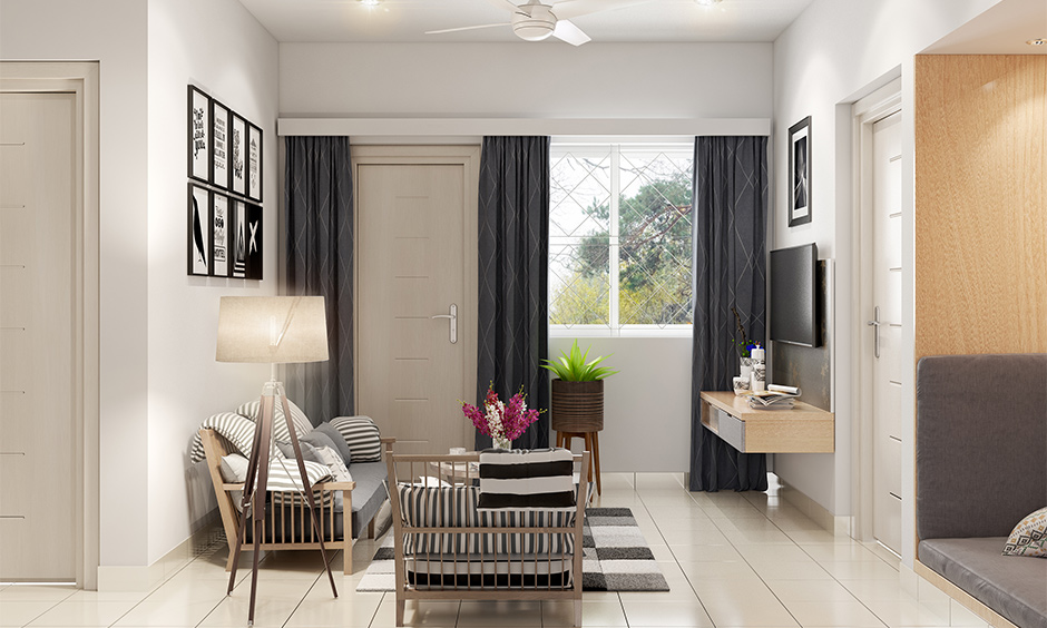 Compact small drawing room decoration with photos, lamp, flowers and potted plants add a bit of charm to space.