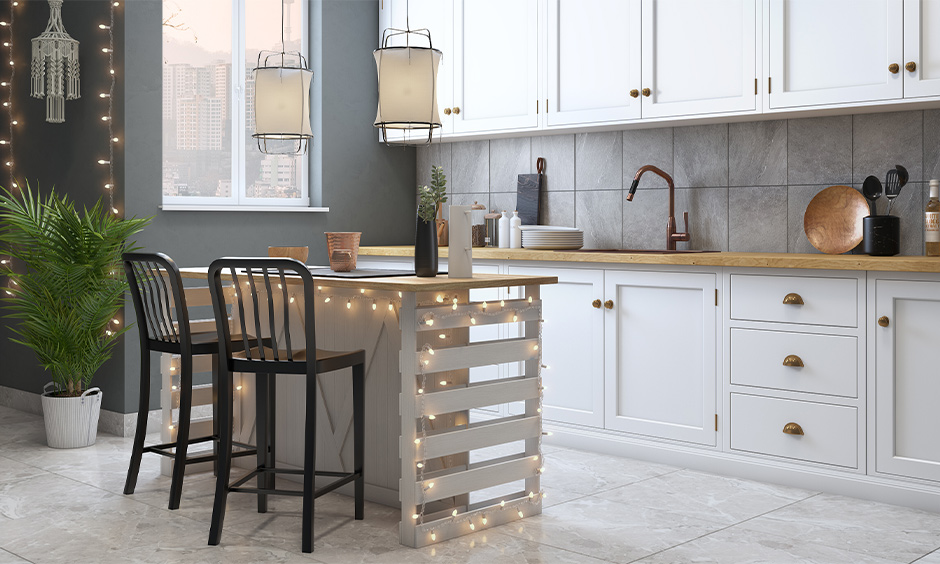 DIY kitchen island lighting, kitchen island decorated with fairy lights and also hanging white lanterns look elegant.