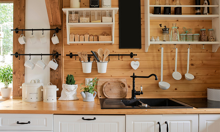 Two hanging kitchen shelves in white with hooks against the wooden wall brings in a farmhouse kitchen look.