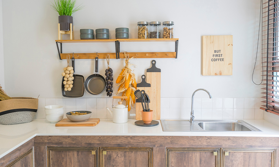 Wall hanging kitchen shelves with hooks made from wooden panels and metal to storage spice jars on and also indoor plants.