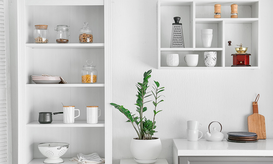 Wall hanging kitchen shelves in white with jars and home decor stacked up looks beautiful is kitchen hanging shelves design.